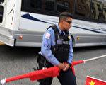 一名警察把親共人士的旗子沒收並折斷。(大紀元)