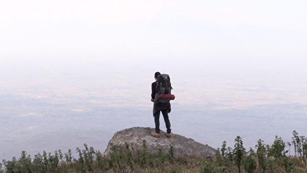 《有任務的旅行》劇照,旅行家謝睿哲登上高峰,俯視馬拉威。(華聯提供)
