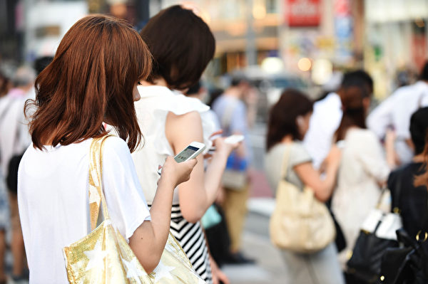 智能手機的流行,處處可見人手一機低頭看訊息。(Atsushi Tomura/Getty Images)