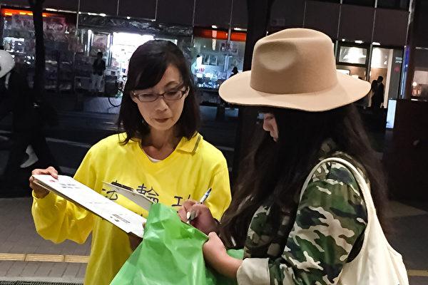 日本各地的法轮功学员在街头向日本民众讲述法轮功受迫害的真相,声援控江。 图为日本熊本县的法轮功学员在街头联署举报的情景。(大纪元图片)