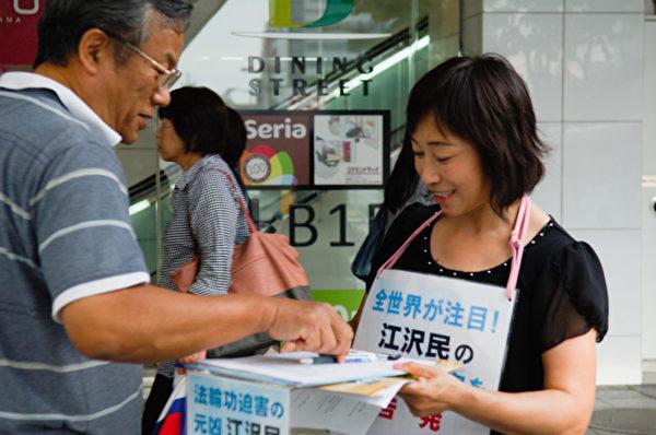 日本各地的法轮功学员在街头向日本民众讲述法轮功受迫害的真相,声援控江。图为日本大阪的法轮功学员在街头联署举报江泽民的情景。(大纪元图片)
