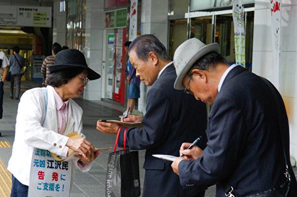 日本各地的法轮功学员在街头向日本民众讲述法轮功受迫害的真相,声援控江。 图为日本大阪的法轮功学员在街头联署举报江泽民的情景景。(大纪元图片)