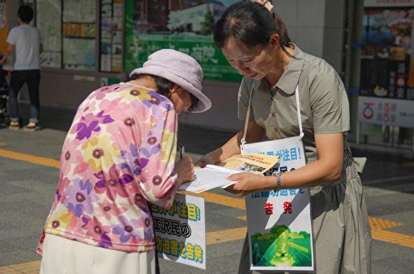 日本各地的法轮功学员在街头向日本民众讲述法轮功受迫害的真相,声援控告江泽民的签名。图为日本大阪的法轮功学员在街头联署举报江泽民的情景。(大纪元图片)