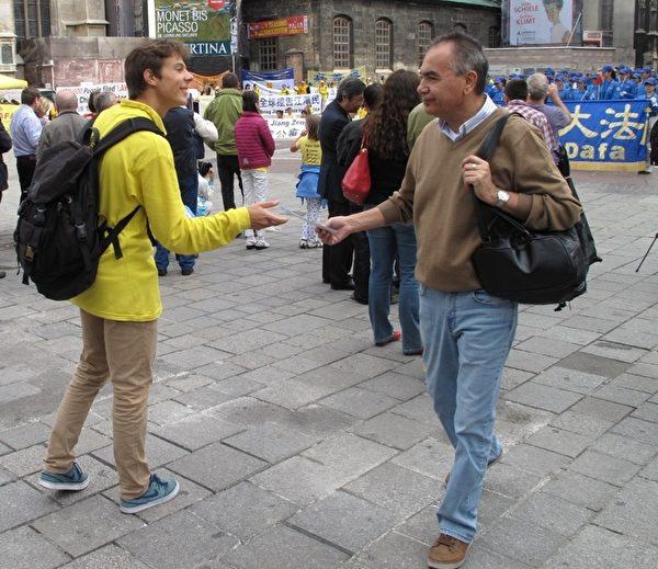 二零一五年九月十九日,在维也纳斯特凡大教堂前广场(Stephansplatz)上,拉托维亚法轮功学员瑞蒙(Raymond)在广场上人群中发传单讲真相。(明慧网)