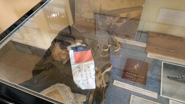 """图片是典藏于北澳达尔文的澳大利亚航空博物馆内的""""血幅""""印有中华民国国旗,并书有""""美国空军 来华助战,仰我军民 一体救护  国民政府航空委员会""""。""""血幅""""是代表中、美在抗战间的情谊,其由来是因抗战时期来华助战的美籍飞行员不会讲也听不懂华语,航空委员会因此发给他们上面写着""""来华助战洋人,军民一体救护""""的血幅,让他们缝在飞行夹克背上,飞行员如果跳伞求生,可寻求中国人民协助,不少飞行员因此能够安然返回部队。(昆士兰台湾中心董幼文主任提供)"""