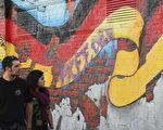 2015年10月2日,德国柏林,人们走过墙上的德国国旗壁画,当日为德国统一25周年前一天。1990年10月3日,在分离41年之后,西德和东德重新统一成一个国家。今年德国将在法兰克福和柏林两地进行欢庆25周年的活动。(Sean Gallup/Getty Images)