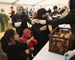 2015年10月8日,德國柏林衛生和社會服務處,志願者正在帳篷裡為中央登記處外尋求庇護的難民分發熱麵食。難民申請後可在此得到住房券和現金。目前,緊急避難所與辦公室對難民每天以幾千人申請的數量持續在增加,已呈現出不堪負荷的現象。(Sean Gallup/Getty Images)