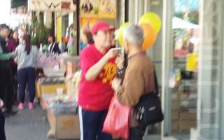 12日,李华红在缅街上指著同情法轮功学员的王先生一直辱骂。(林丹/大纪元)