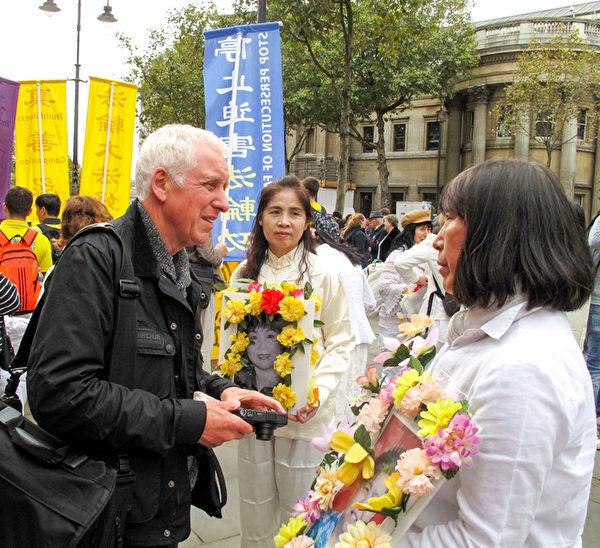 图3:十月十日下午,住在伦敦附近的英格兰摄影师基思(Keith)路过伦敦圣马丁广场,被法轮功学员声援诉江、讲真相反迫害集会展现的真相所吸引。(明慧网)