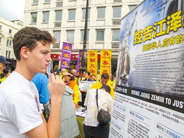 图5:二零一五年十月十日,伦敦青年本(Ben)在伦敦圣马丁广场第一次看到法轮功,签名谴责中共活摘罪行后,站在声援控江的真相展板前认真阅读。(明慧网)