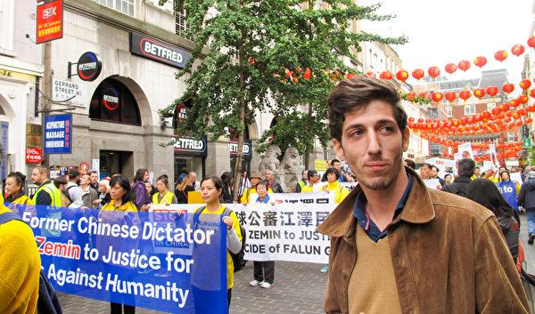 图6:二零一五年十月十日,现住布里斯托的法国青年乔(Joe)在伦敦唐人街上看到法轮功学员的游行,表示支持理解控江大潮。(明慧网)