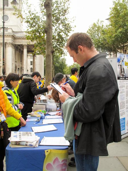 图7:二零一五年十月十日,在剑桥大学教法律的约翰(John)在伦敦圣马丁广场签名谴责中共活摘罪行,他还表示让更多的人听到全球公审江泽民的信息非常重要。(明慧网)