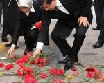 土耳其总理达夫托葛鲁14日说,首都安卡拉上周末发生的连环爆,凶手恐涉IS和PKK。图为13日,达夫托葛鲁(右)和他的妻子将红色康乃馨放在安卡拉爆炸事件现场。(Hakan Goktepe/TURKISH FOREIGN MINISTRY/AFP)