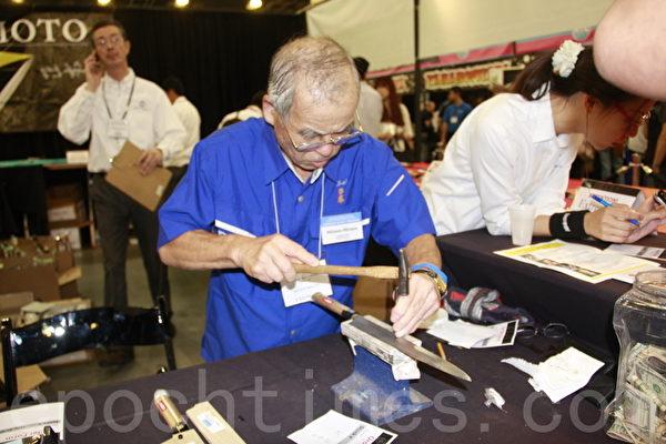 擁有數十年製刀經驗的日本老師傅現場為民眾購買的刀具刻字。(徐曼沅/大紀元)