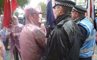 """周三中午左右,一群拿着血旗的""""欢迎者""""想挤在法轮功学员前面,英国警察让他们立刻回去。(高峰/大纪元)"""
