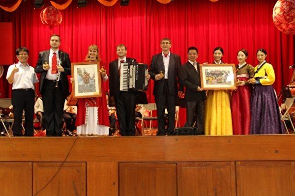 市长江聪渊赠送今年宜兰市大拜拜摄影得奖作品给外国乐团。(谢月琴/大纪元)