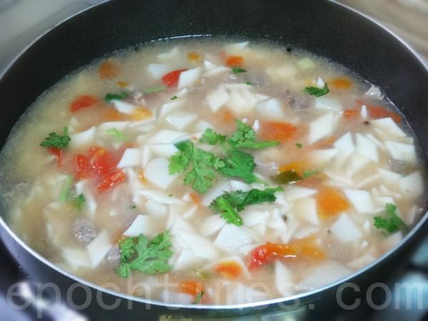 锅中加入牛骨汤,下面稍煮,依续下软扁豆、臊子、胡椒粉、香菜煮熟。(彩霞/大纪元)