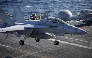 """2015年10月28日,韩美海军于10月26日至29日期间在韩国东部海域进行韩美联合海上机动训练。此次军演美国派出了最新的核动力航母""""罗纳德.里根""""号。图为一架美国海军F/A-18超级大黄蜂战斗机在航空母舰罗纳德·里根号的甲板上降落。(Kim Hong-Ji/AFP)"""