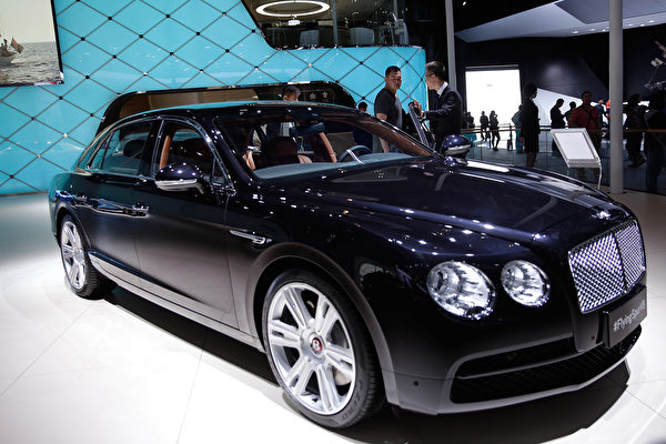 BEIJING, CHINA - APRIL 22:  The potential consumer stands beside a Bentley Flying Spur V8 car car during the 2014 Beijing International Automotive Exhibition at China International Exhibition Center on April 22, 2014 in Beijing, China. More than 2,000 automotive enterprises from 14 countries and regions participated in the 2014 Beijing International Automotive Exhibition from April 20 to April 29.  (Photo by Lintao Zhang/Getty Images)
