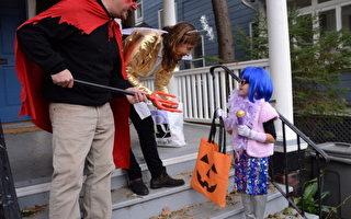 """10月30日晚上,3名女孩,在圣安娜(Santa Ana)居民区参加""""给糖或捣乱""""(trick-or-treaters)活动时﹐被一辆超速行驶的汽车撞死。图为美国纽约万圣节要糖的小姑娘。 (Stephen Lovekin/Getty Images)"""