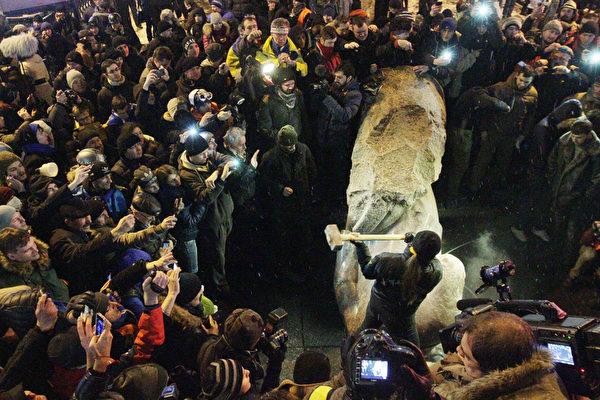 2013年12月8日,乌克兰首都基辅,市中心的一座列宁塑像被推倒后,民众拿槌子将其破坏。乌克兰民众从此在全国掀起推倒列宁雕像的弃共行动,表明了乌克兰人对马列共产主义的厌恶和憎恨。(ANATOLI BOIKO/AFP)