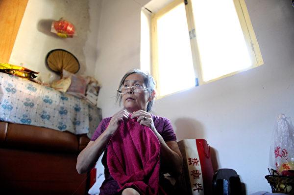 2012年9月4日,吳瑞(音譯)在北京的家中默默地織著毛衣。當她12歲的女兒故去後,她不僅失去了唯一的孩子,還失去了養老的保障。(WANG ZHAO/AFP/Getty Images)