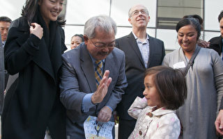 11月4日,旧金山市米慎街1400号的15层可负担公寓楼建成开售,图为旧金山市长李孟贤(左起2)欢迎一家人入住,收到孩子的礼物后,与孩子击掌。(周凤临/大纪元)