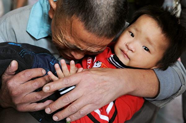 2009年10月29日,王邦銀(音譯)抱著被解救回來的兒子失聲痛哭。(STR/AFP/Getty Images)
