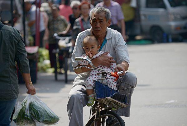 2015年9月8日,一個老人抱著一個孩子,騎車走在北京的街頭上。單憑老齡化這一點,所謂的「計生」好處就不可能實現。(WANG ZHAO/AFP/Getty Images)