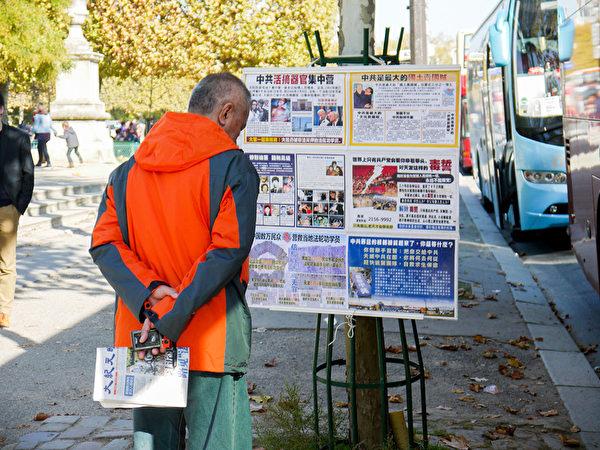 巴黎景点上,大陆游客观看法轮功真相展板。(明慧网)