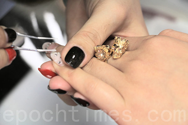 美甲師小張在給客人指甲黏上亮鑽。(李霖昭/大紀元)