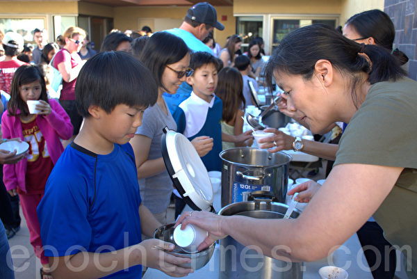 2015年11月22日,加州圣地亚哥中华学苑又迎来了一年一度的汤圆节,让学生了解冬至吃汤圆的习俗。图为家长给下课的学生们盛汤圆。(杨婕/大纪元)