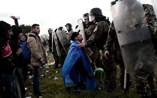 11月26日,一名欲入境马其顿的移民,跪求马国边境警察。(ANGELOS TZORTZINIS/AFP)
