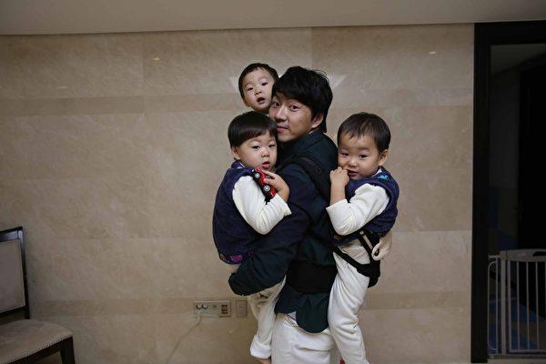 宋一國抱著三胞胎,慈父形象被封為松島聖人。(中天提供)