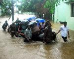 印度清奈近日受到新一輪的暴雨侵襲,在淹水近半個月還未全退之際,從週一(2015年11月30日)開始又下起連日暴雨,讓整個城市變成一片汪洋,迫使機場與火車停運、學校關閉。本圖為1日有多名志願工作者助受困居民撤離災區。(STRDEL/AFP/Getty Images)