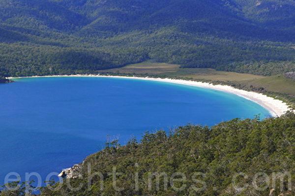 酒杯灣彎曲圓弧的外形,潔白沙灘、湛藍的海水清澈透明猶如盛著純釀的晶瑩酒杯,構成了一幅令人難忘的畫面,讓人陶醉。(華苜/大紀元)