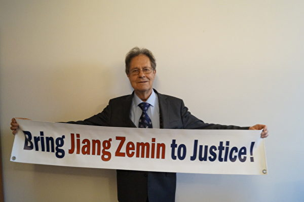 """欧洲议会议员克劳斯‧布赫纳教授(Prof. Dr. Klaus Buchner)手举 """"法办江泽民!""""的横幅。(大纪元)"""