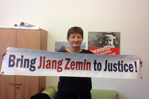 """欧洲议会议员科妮莉亚‧恩斯特博士(Dr. Cornelia Ernst)手举""""法办江泽民!""""的横幅。(大纪元)"""