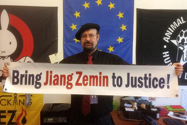 """欧洲议会议员斯蒂芬‧埃克(Stefan Eck)手举""""法办江泽民!""""的横幅。(大纪元)"""