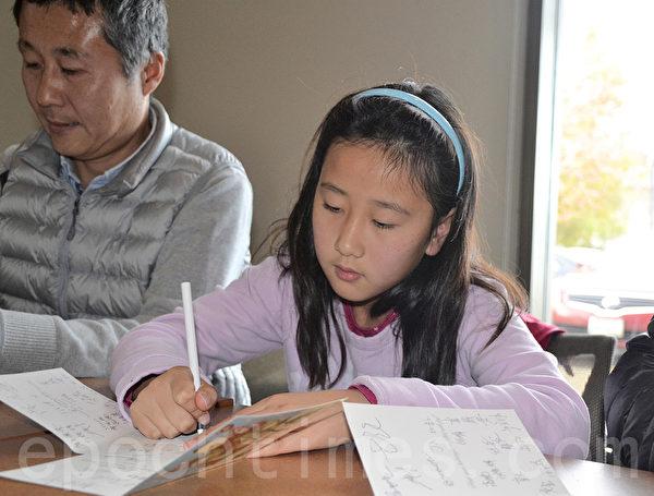 小姑娘Selena隨父母一起來為獄中良心囚犯寫賀卡。(梁博/大紀元)