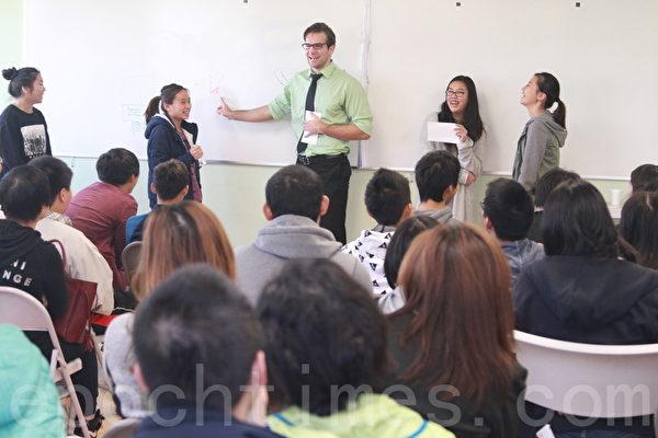 ACI丹尼爾老師帶領學生們做遊戲以促進孩子們溝通、表達與想像的能力。(張岳/大紀元)