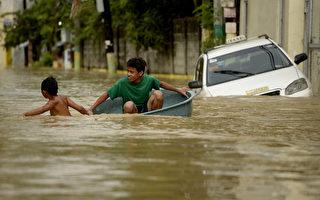 茉莉台风(Melor)肆虐菲律宾,首都马尼拉附近有数万民众今天在水深及腰的农地跋涉,然而另1个风暴恐将带来更多雨量。图为12月18日,两个孩子用大盆当船在水中划。(NOEL CELIS/AFP/Getty Images)