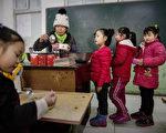 2015年12月18日,中国北京,农民工子女们在课桌旁排队等午餐,这些随父母进京的农民工子女大多只能就读非正式的学校。研究显示无论是跟父母进城的﹐还是随爷爷奶奶留守农村的农民工子女,在义务教育方面都存在严重问题。(Kevin Frayer/Getty Images)