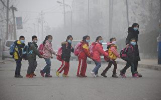 2015年12月24日,山東省濟南,成群學生戴著口罩由大人帶領走在過街的路上。因霧霾範圍持續擴大,中國東部嚴重的空氣污染使得京津冀及周邊地區當天發布紅色預警的城市有10個。(AFP)