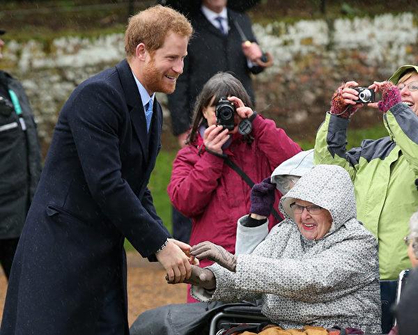 哈里王子冒着小雨和路边等候的一些民众交谈,包括两个年幼的孩子和一个坐在轮椅上的老妇人。(Chris Jackson/Getty Images)