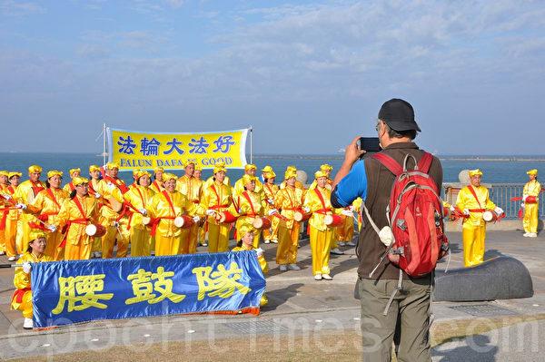 大陸遊客驚豔於法輪功腰鼓隊表演,拿起手機拍照留念。(李晴玳/大紀元)