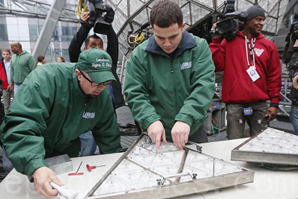 地標公司的Nick Bonavita(左)和Jason Andrle(右)在把最後幾塊水晶板安裝到模塊上,然後安裝到球上。(杜國輝/大紀元)