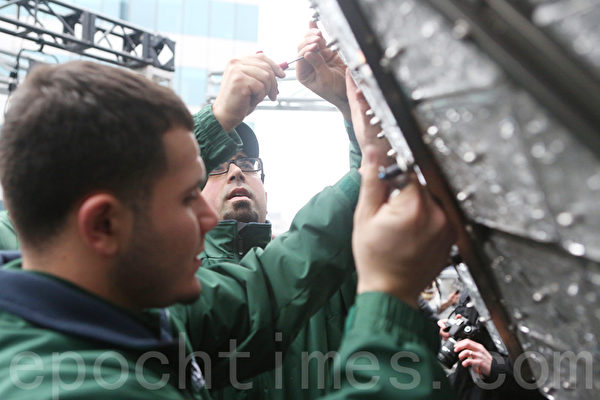 兩位工人在用螺絲把模塊固定到水晶球上。(杜國輝/大紀元)