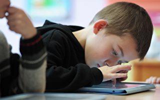 心理学家认为,用电子产品分散孩子的注意力,并不能让他们学会控制和调整情绪。(FREDERICK FLORIN/AFP/Getty Images)