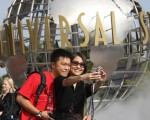 YouTube上传影片统计的全球热门10大求婚地点。图为中国游客在洛杉矶环球影城摄影留念。(ROBYN BECK/AFP/Getty Images)